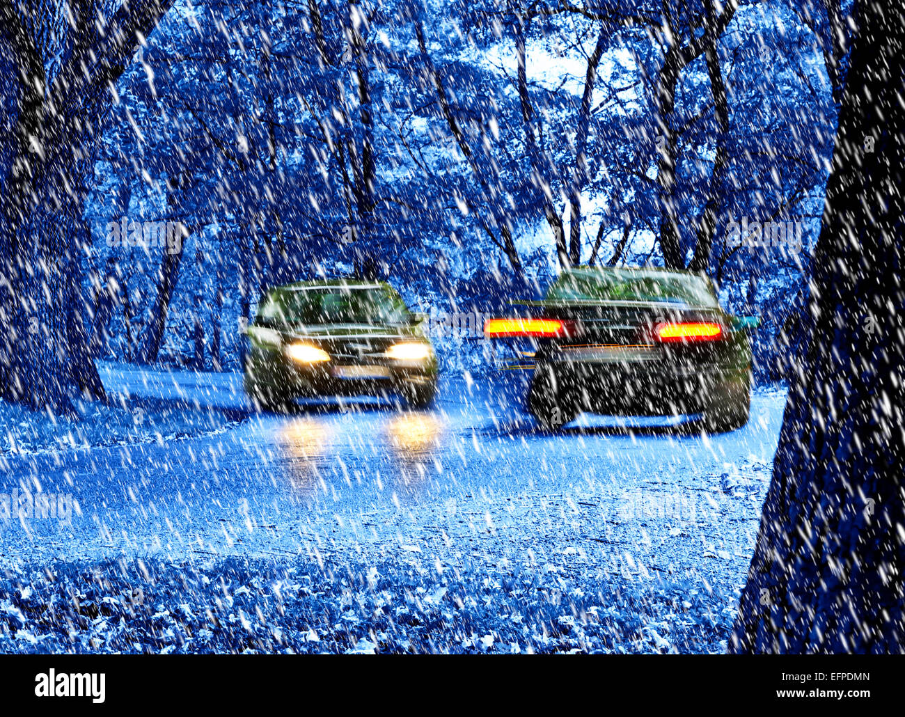 two cars moving in the snow fall by night - Stock Image