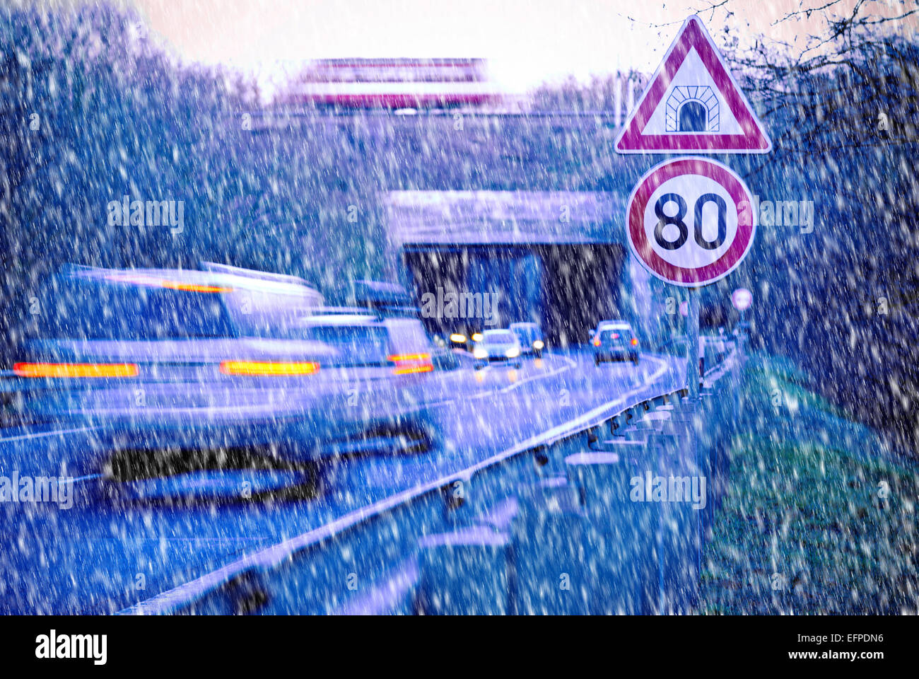 cars on the road with tunnel in the snow fall - Stock Image