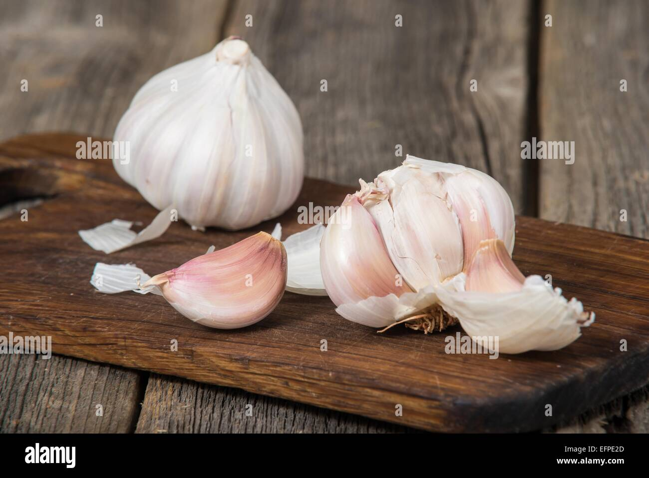 Garlic on old wooden breadboard Stock Photo