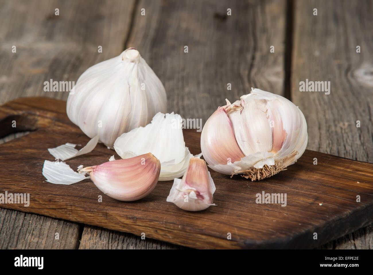 Garlic on old wooden breadboard Stock Photo