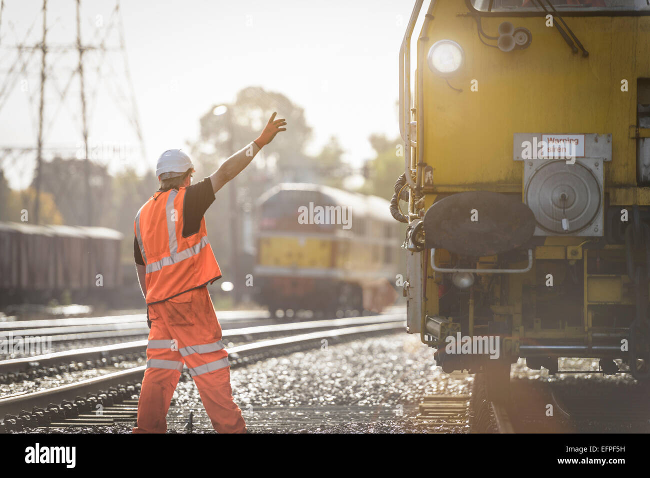 Maintenance worker signalling to train on railway - Stock Image