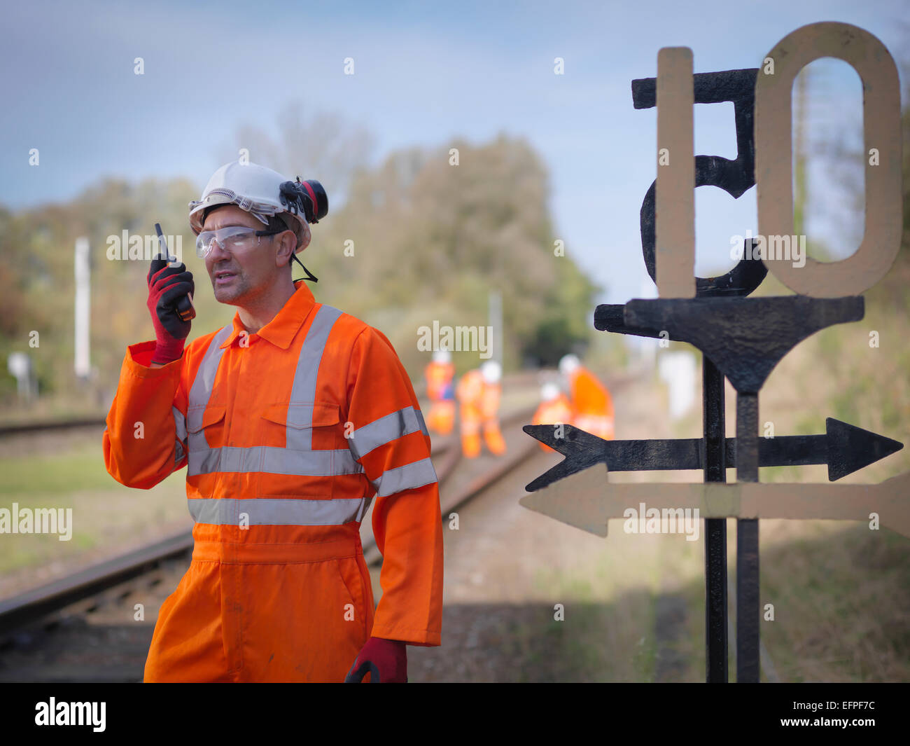 Railway worker using walkie talkie on railway track - Stock Image