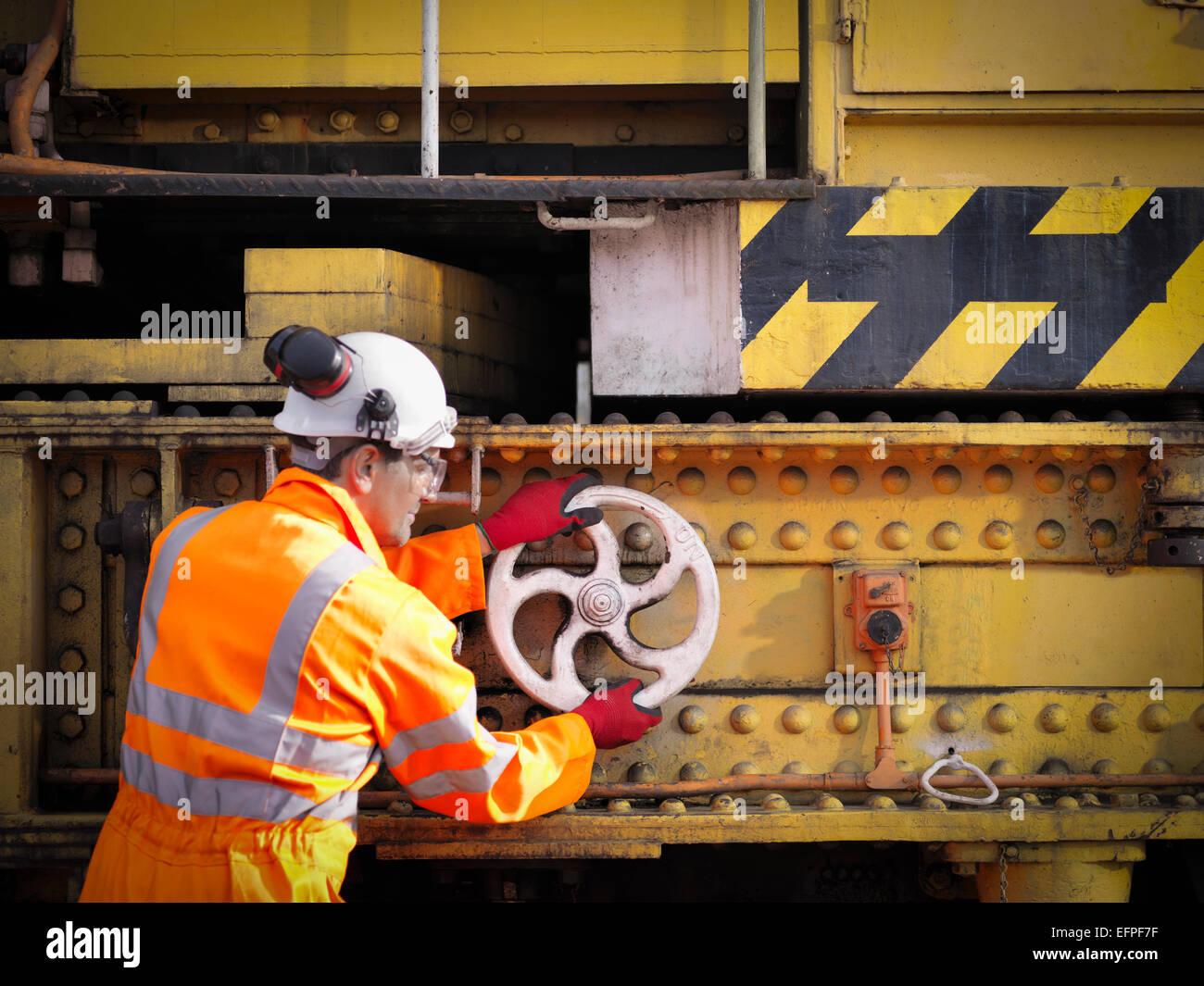 Railway worker turning wheel on maintenance train on railway - Stock Image