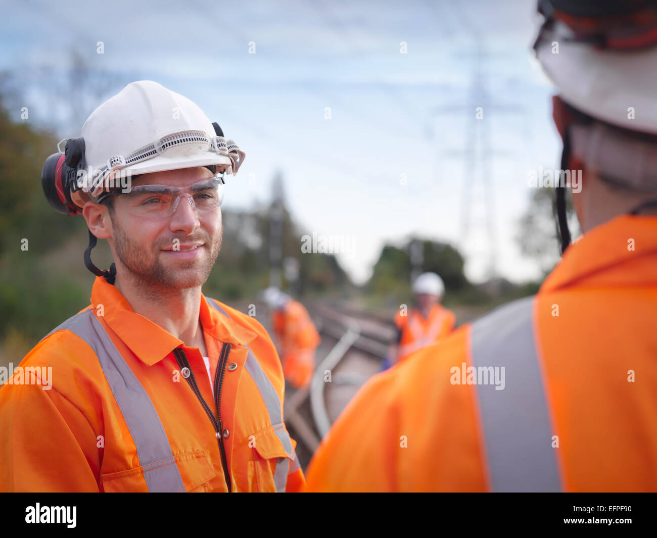 Portrait of apprentice railway maintenance worker in discussion on track - Stock Image