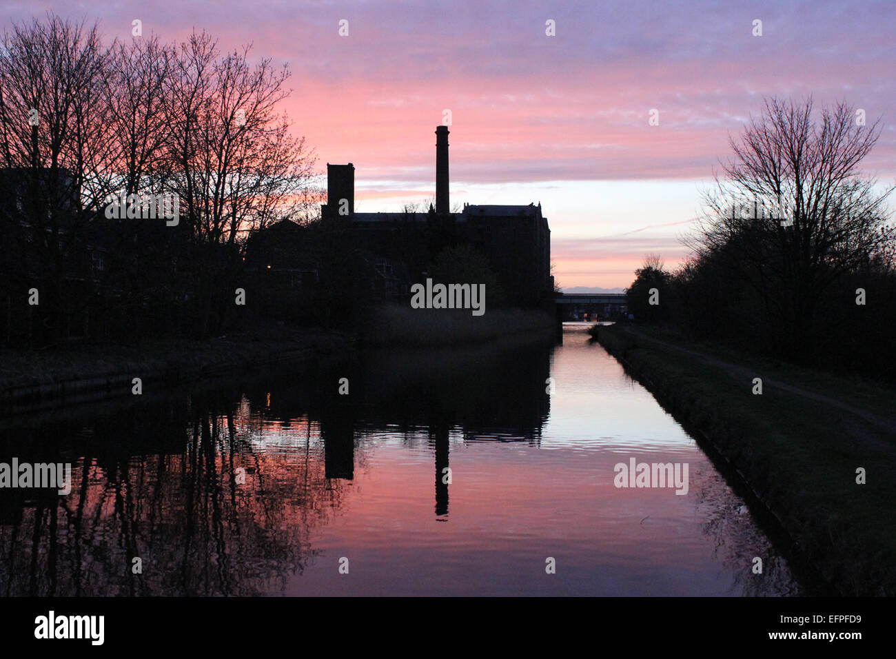 Burscough mill is silhouetted and reflected in The Leeds and Liverpool canal at dusk. - Stock Image