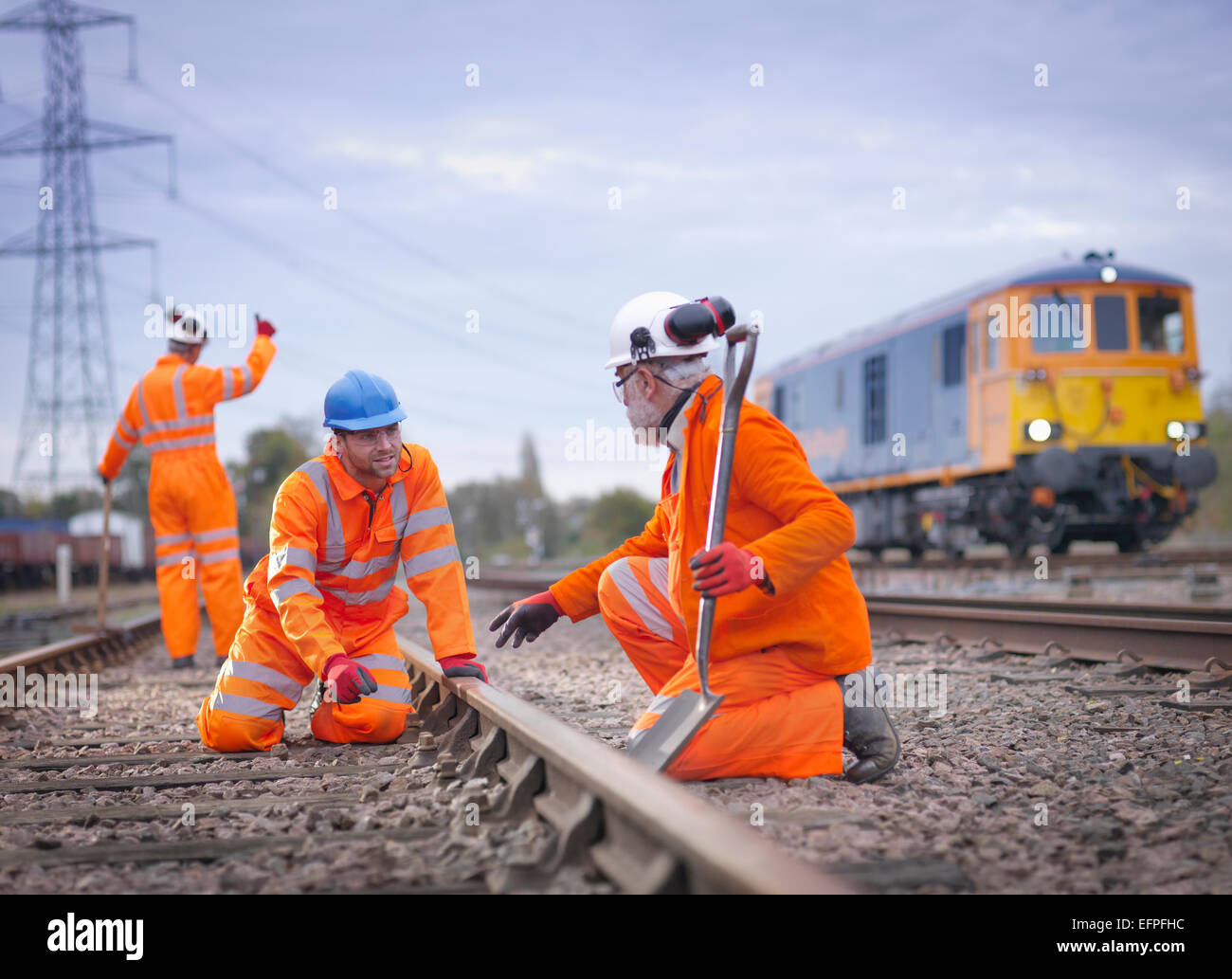 Apprentice railway worker instructed by engineer on railway - Stock Image