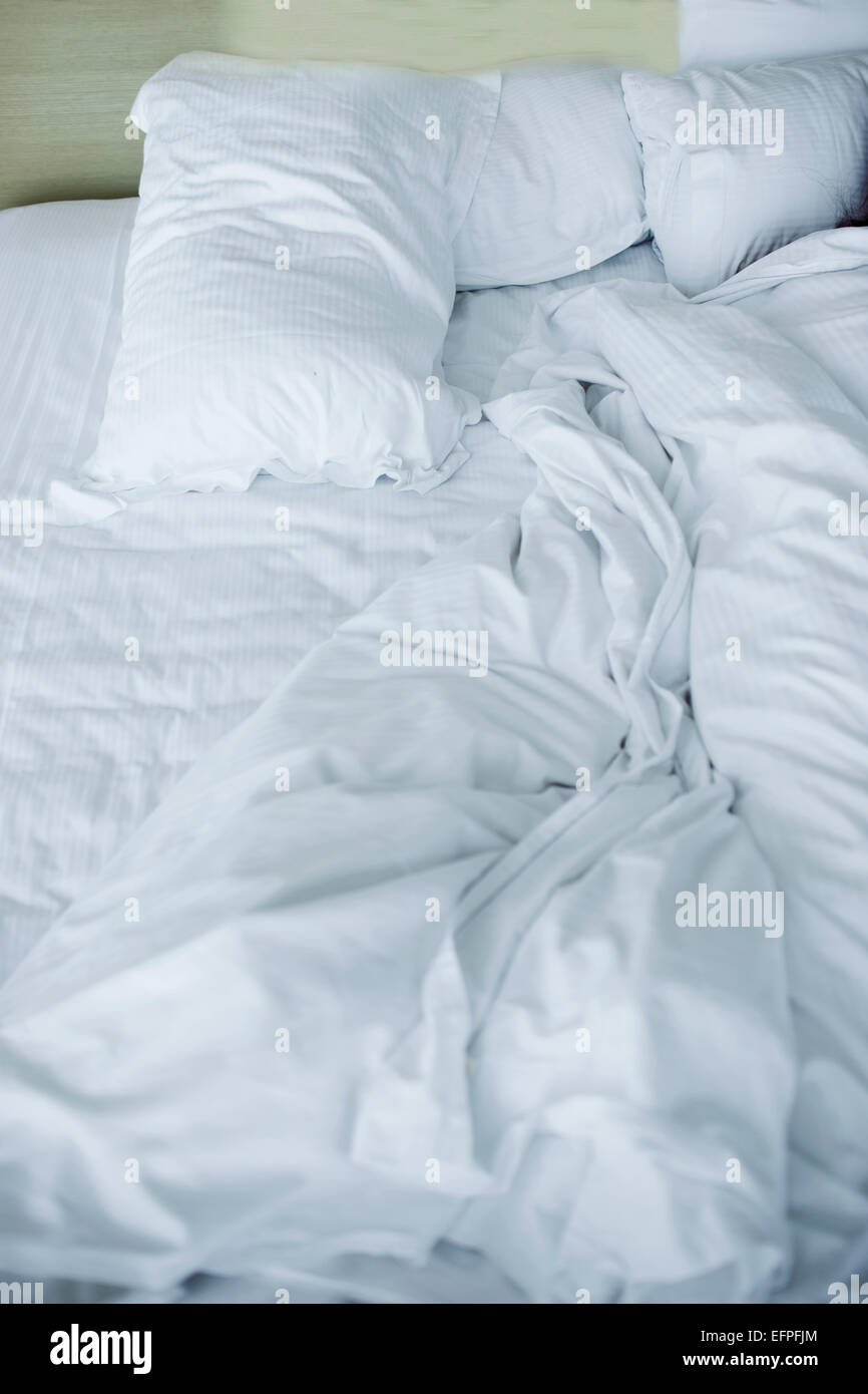 Unmade double bed with white pillows and duvet - Stock Image