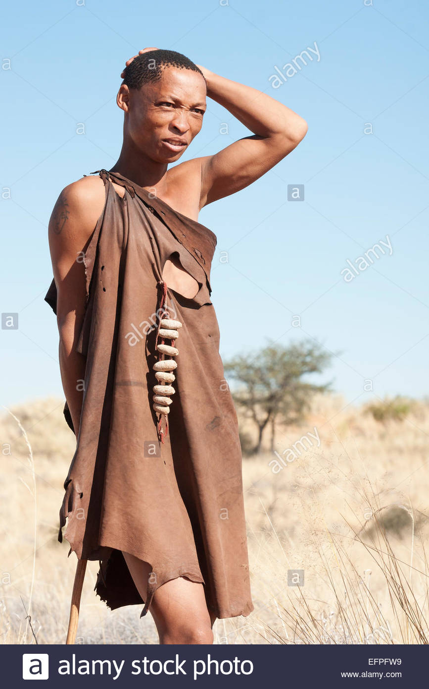 Bushman wearing an animal skin leather tunic stands with hand on head looks across plains on a hunt in the Kalahari, - Stock Image