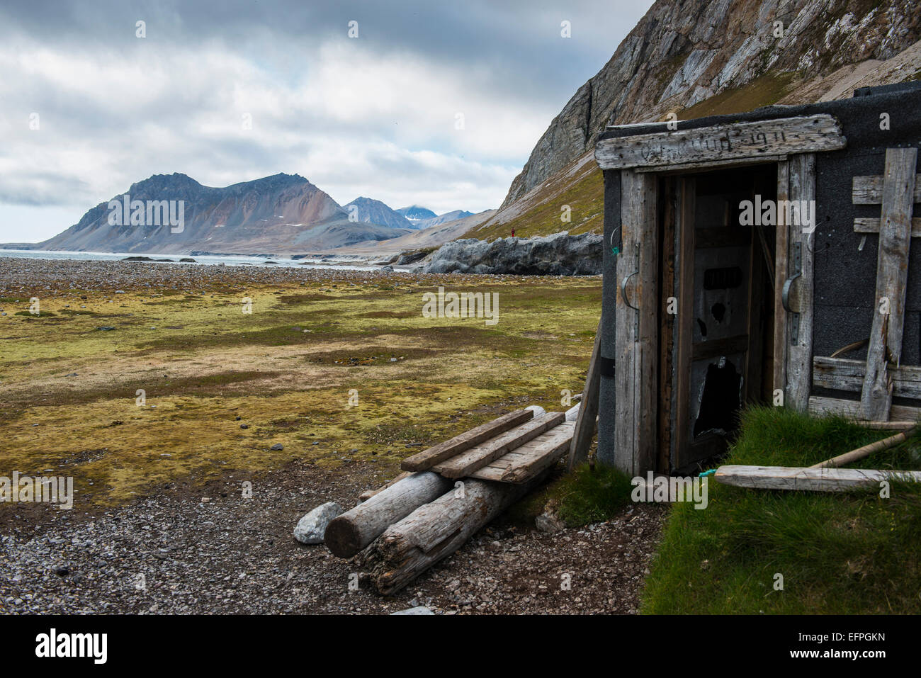 Abandoned hut on Alkhornet with a huge rock in the background, Svalbard, Arctic - Stock Image