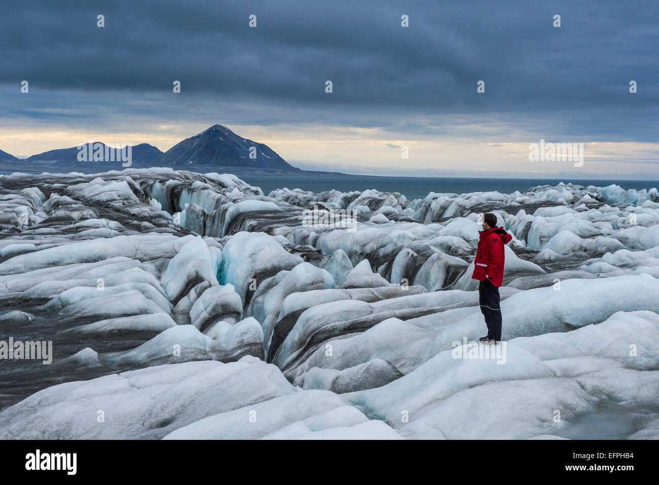 Man standing on a huge glacier in Hornsund, Svalbard, Arctic, Norway, Scandinavia, Europe - Stock Image