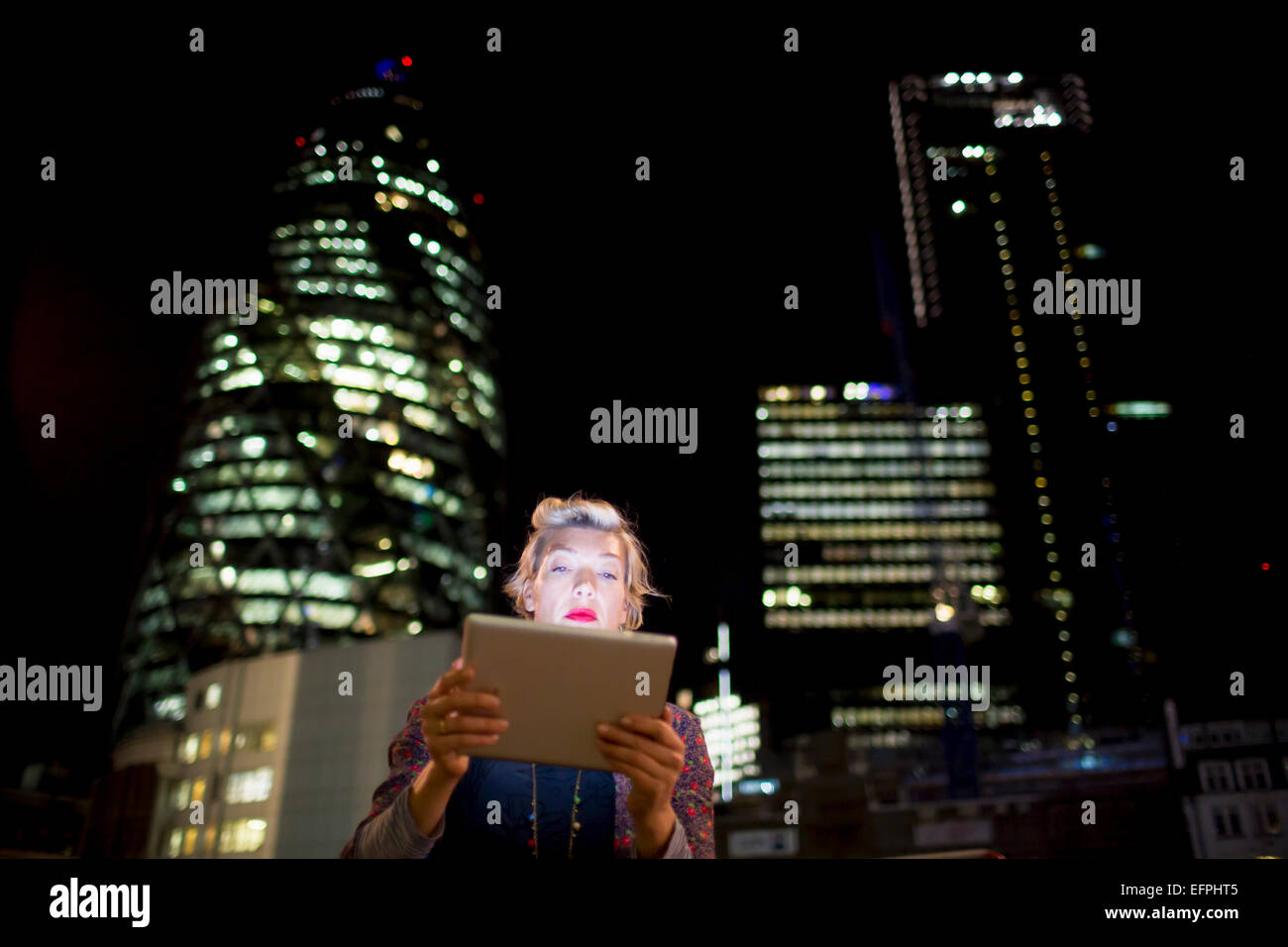 Mature woman in front of office buildings using digital tablet at night, London, UK - Stock Image