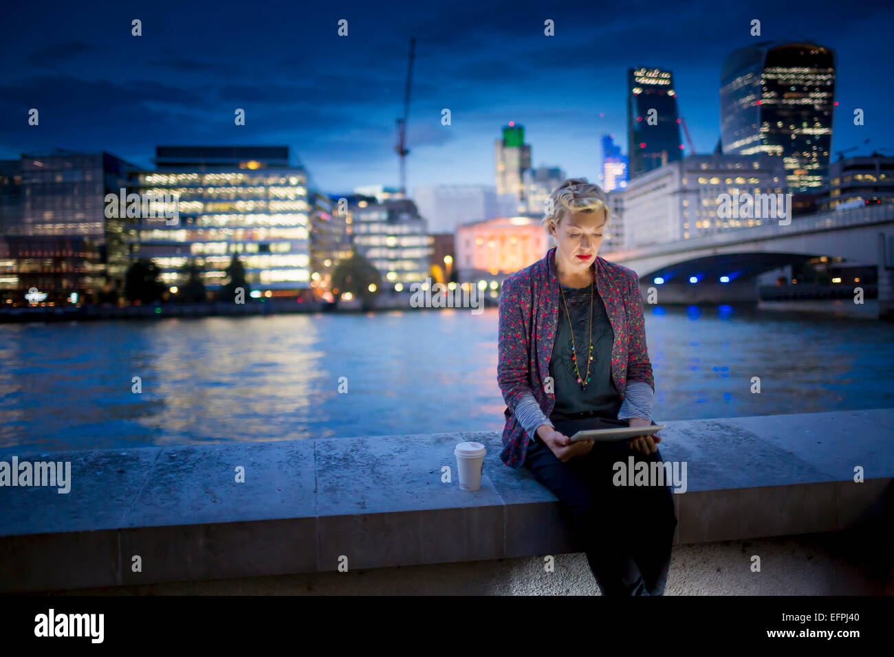 Mature businesswoman sitting on Thames waterfront using digital tablet at night, London, UK - Stock Image