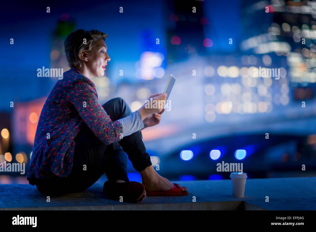 Mature businesswoman sitting on waterfront using  digital tablet at night, London, UK - Stock Image