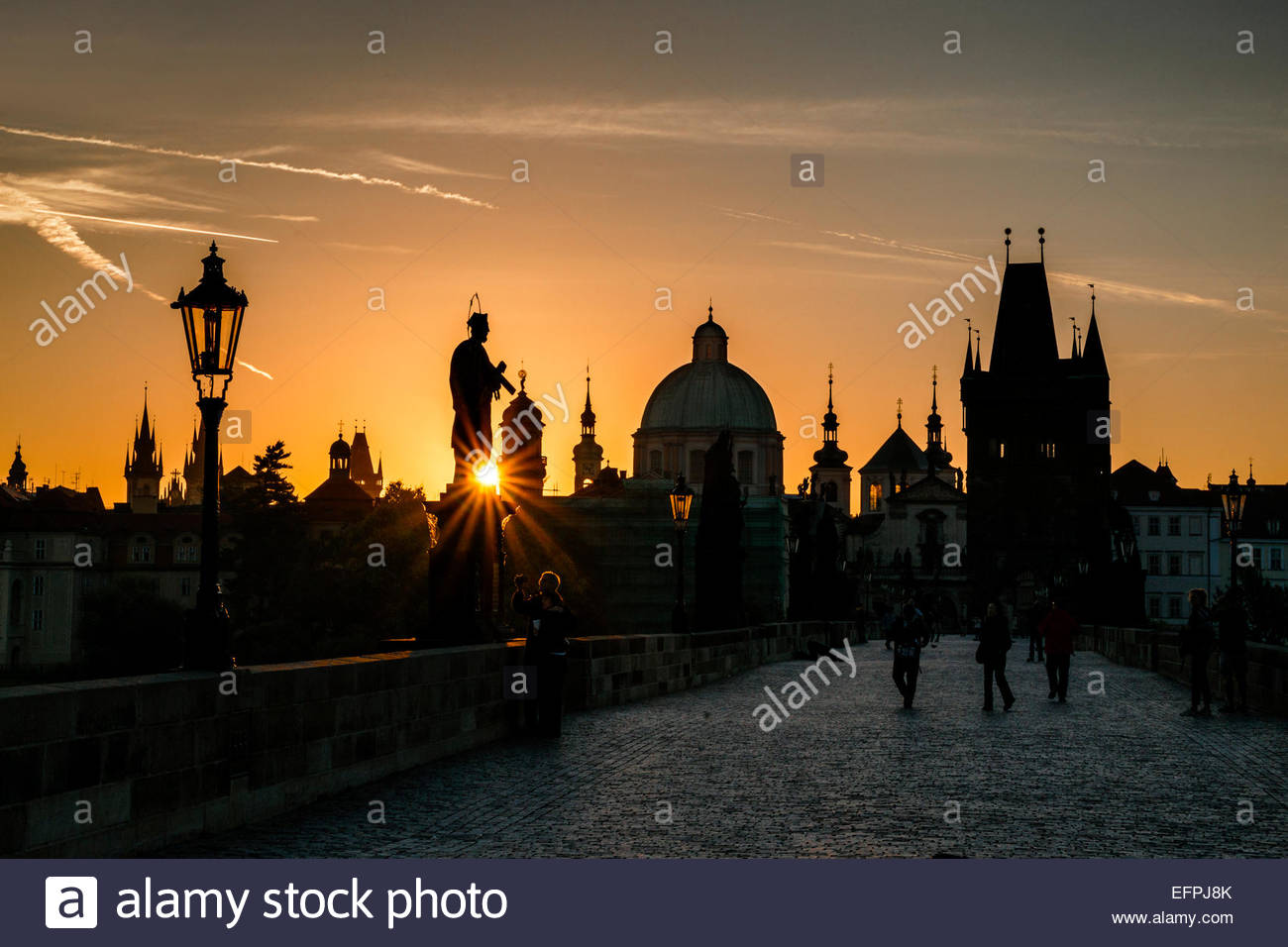 Starburst on silhouetted statue on Charles Bridge from low setting sun, UNESCO World Heritage Site, Prague, Czech - Stock Image