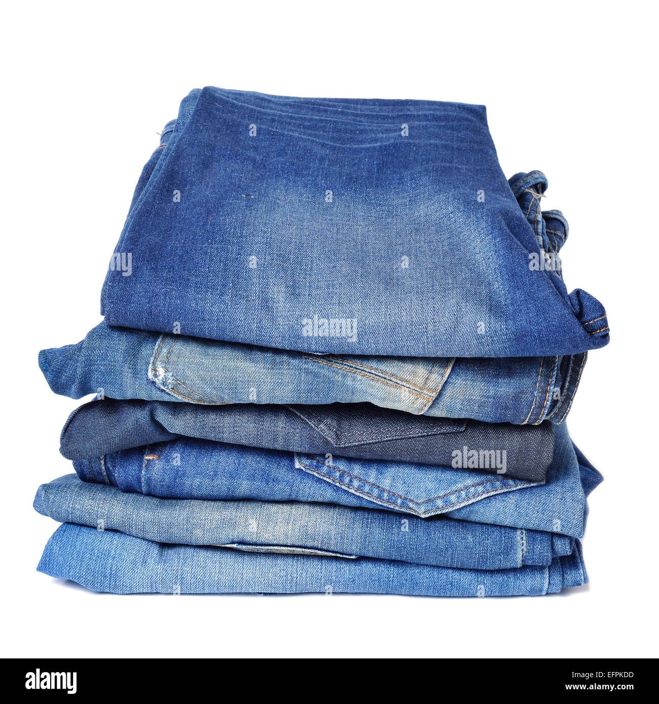 a pile of folded blue jeans on a white background - Stock Image