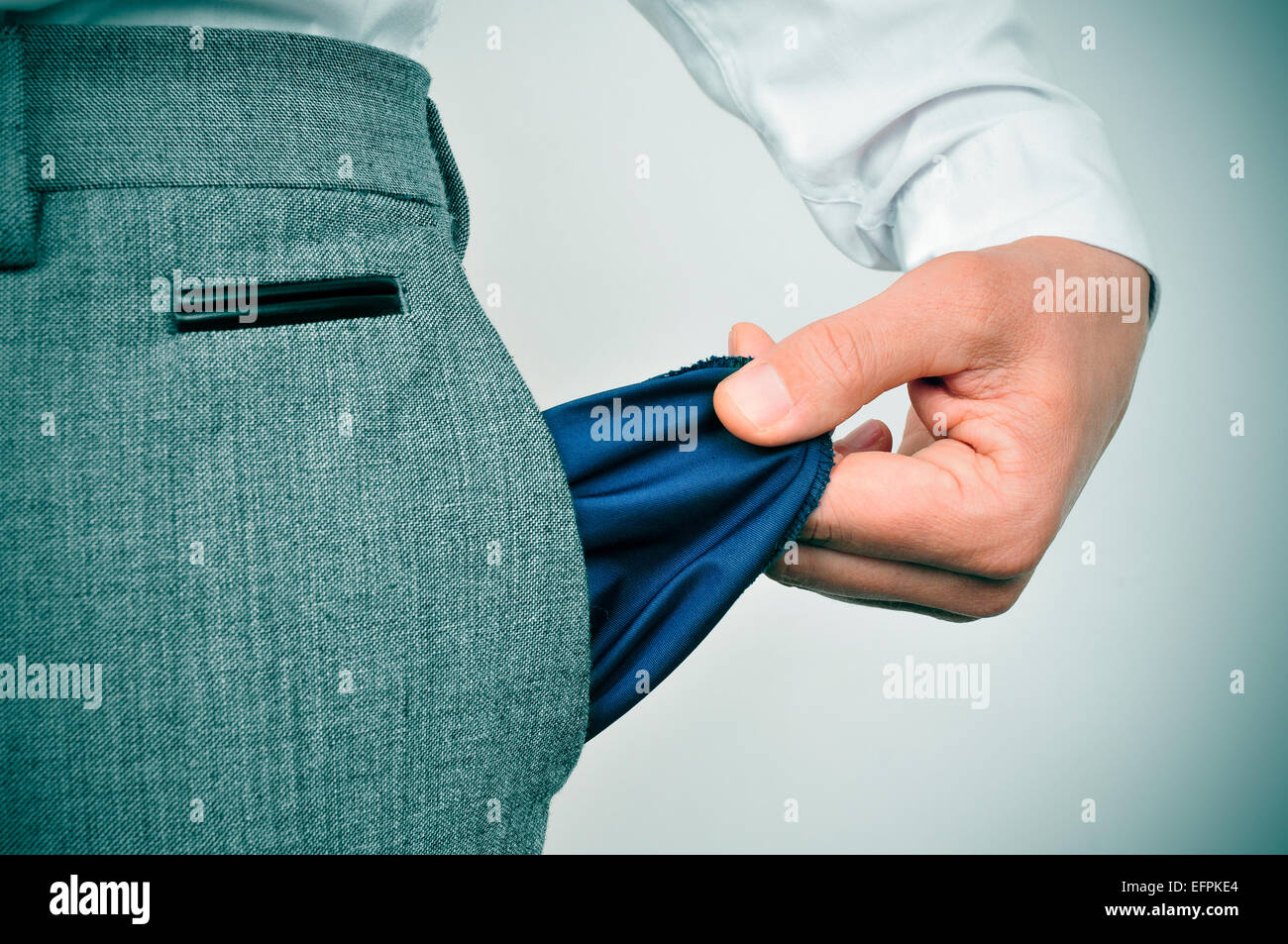 a broke businessman showing his empty pocket - Stock Image