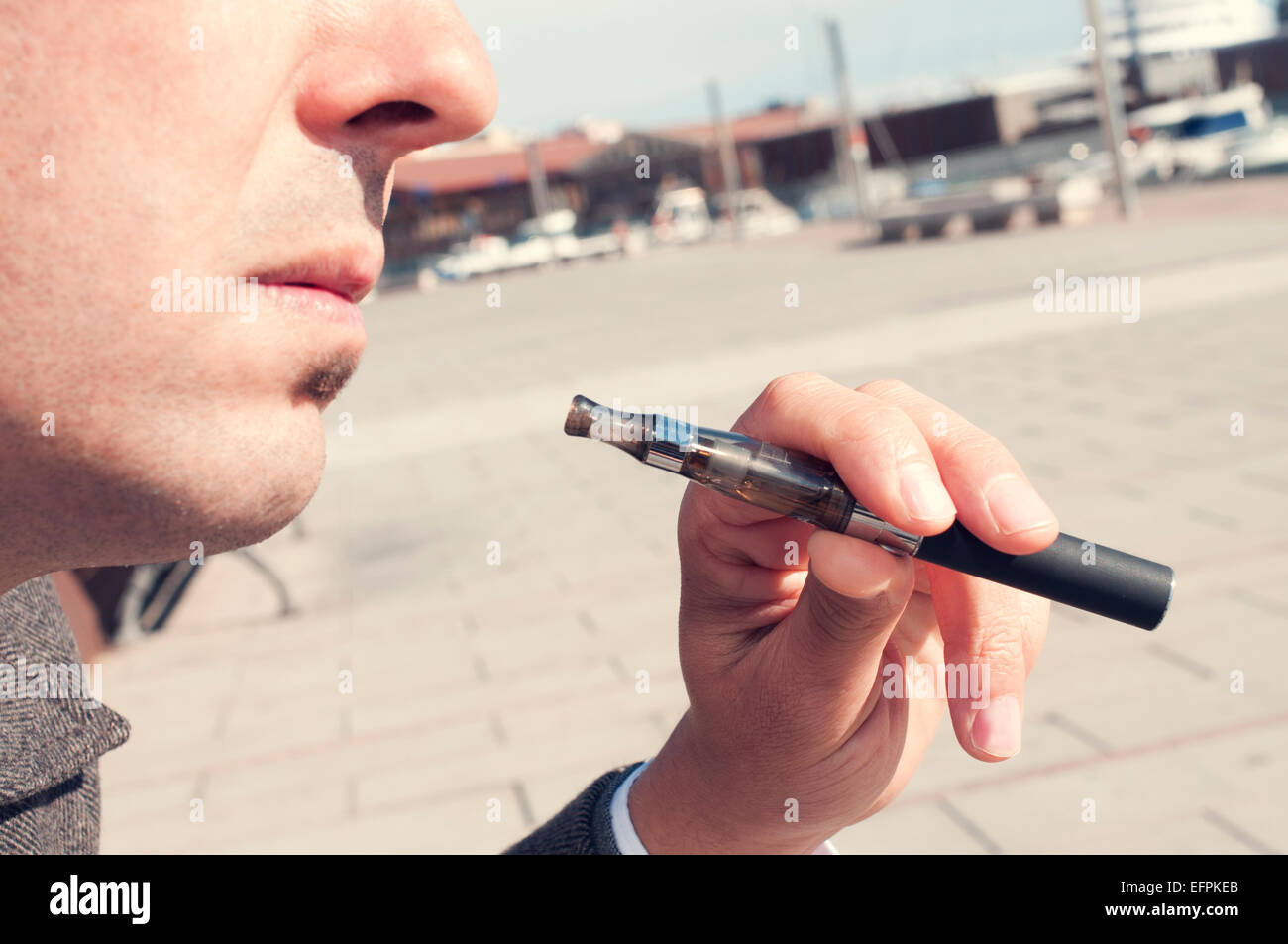 a young man vaping with an electronic cigarette - Stock Image