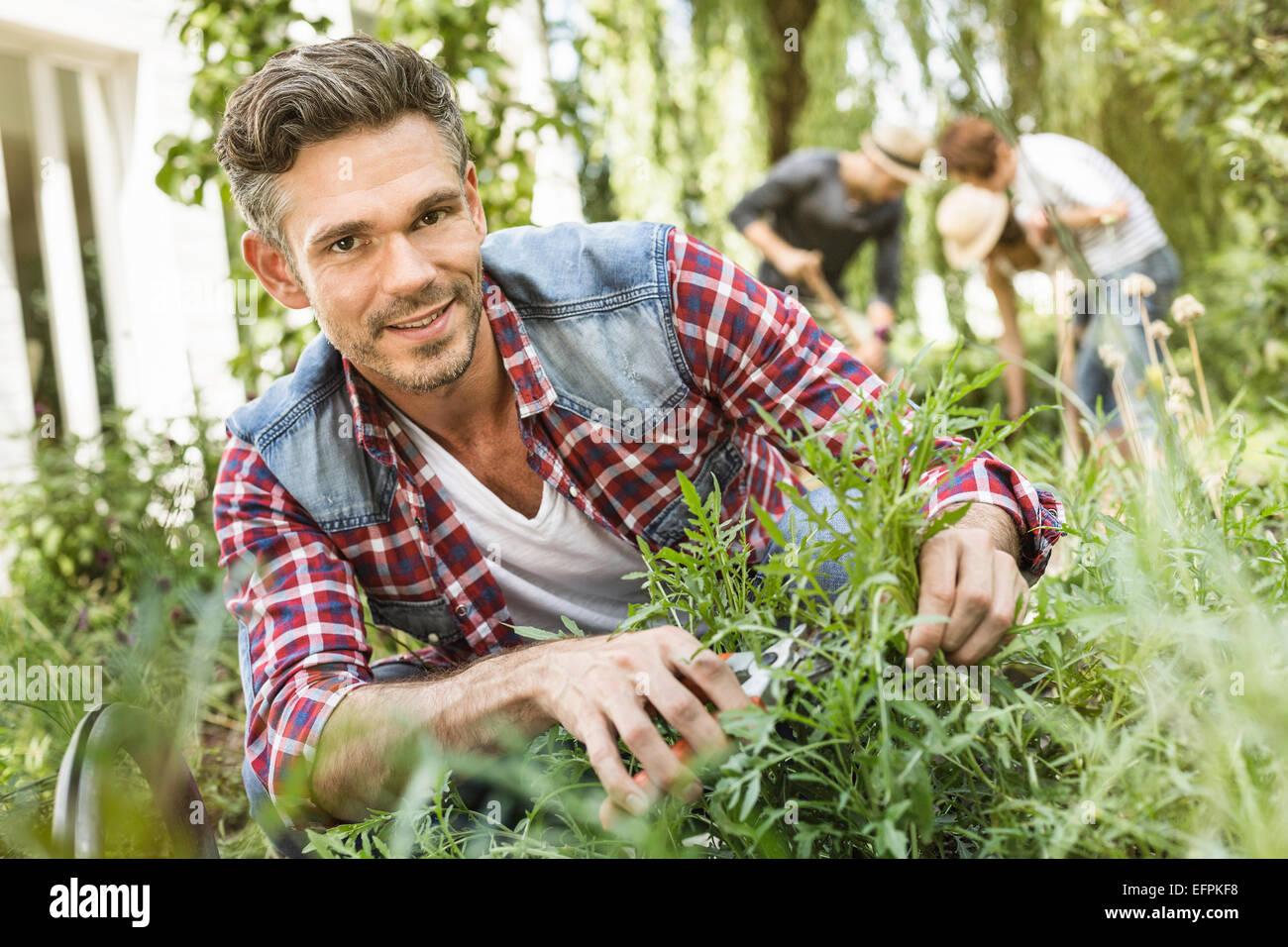 Mid adult man tending to plants in garden - Stock Image