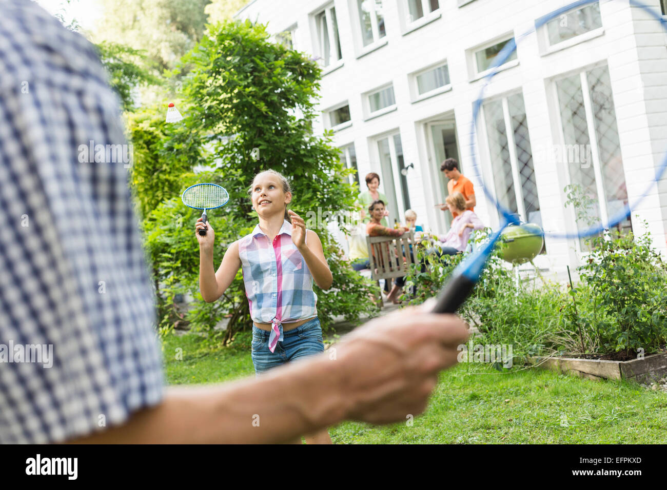Girl and male relation playing badminton while family look on - Stock Image