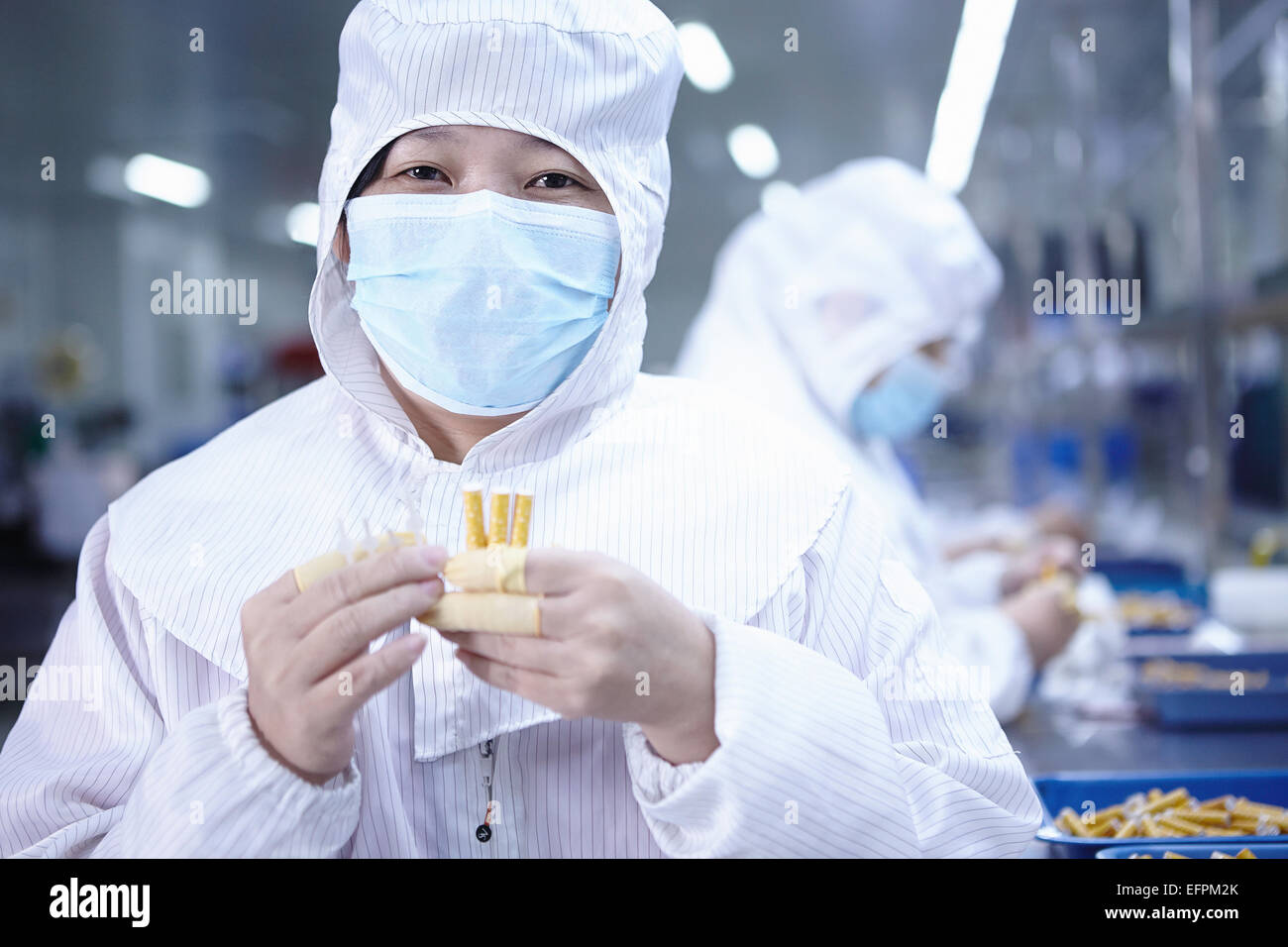 Portrait of worker holding ecgarettes in ecigarette factory - Stock Image