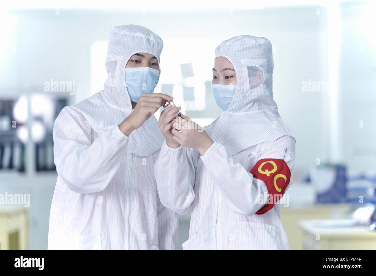 Colleagues looking at ecigarette in ecigarette factory - Stock Image