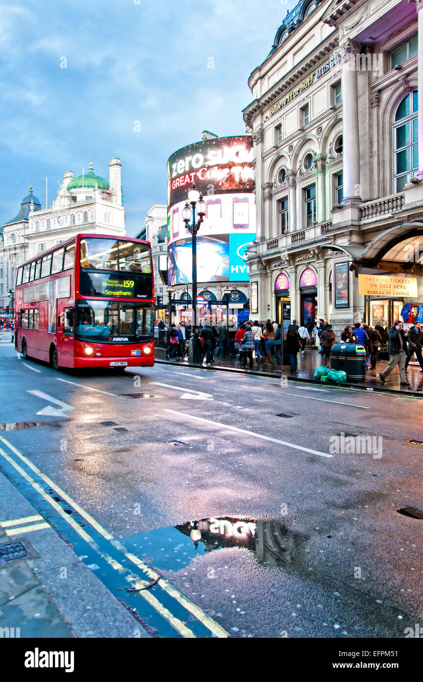 London, United Kingdom - April 12, 2013: Piccadilly Circus neon signage reflected on street with typical double - Stock Image