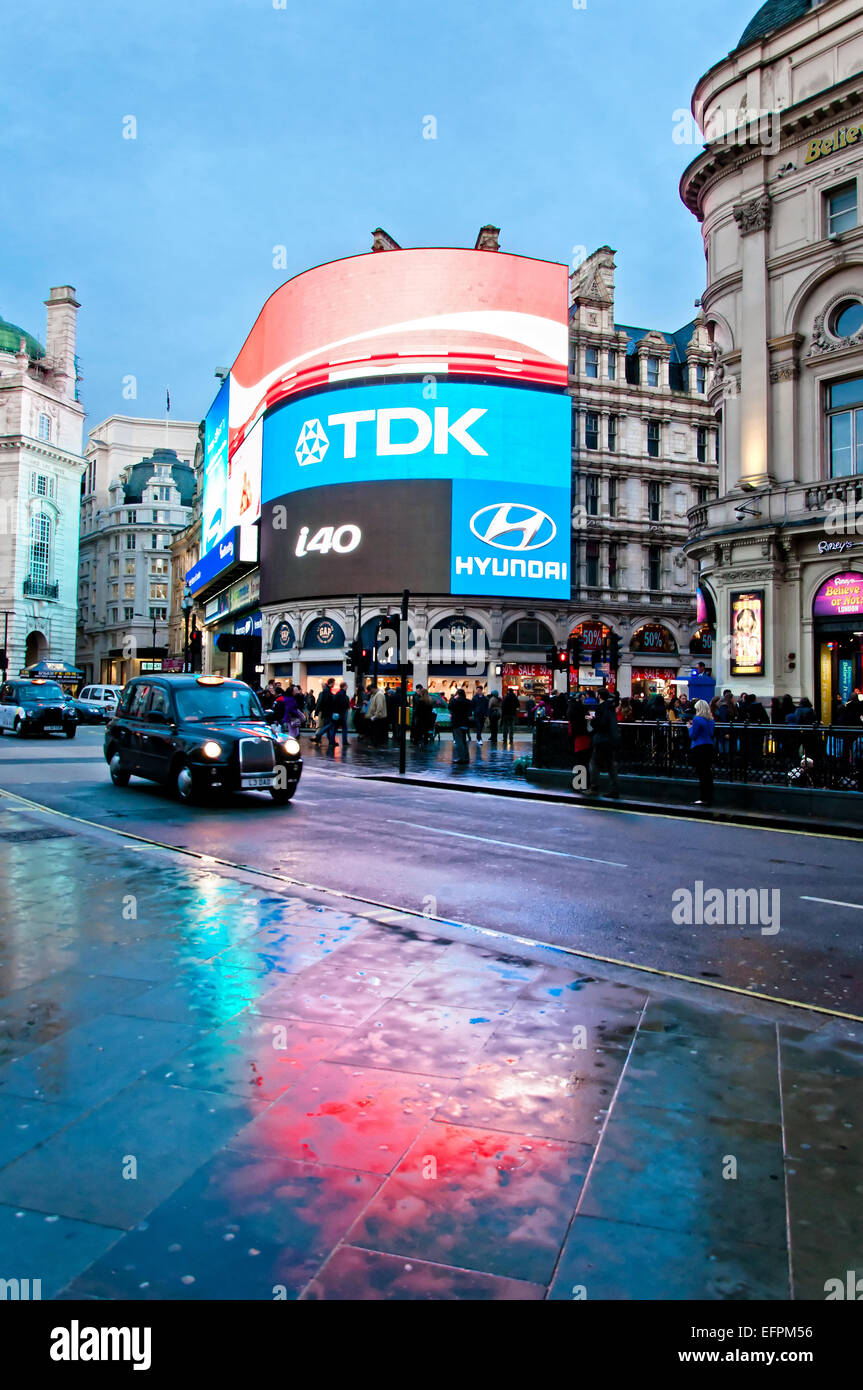 London, United Kingdom - April 12, 2013: famous Piccadilly Circus neon signage reflected on street with taxi in - Stock Image