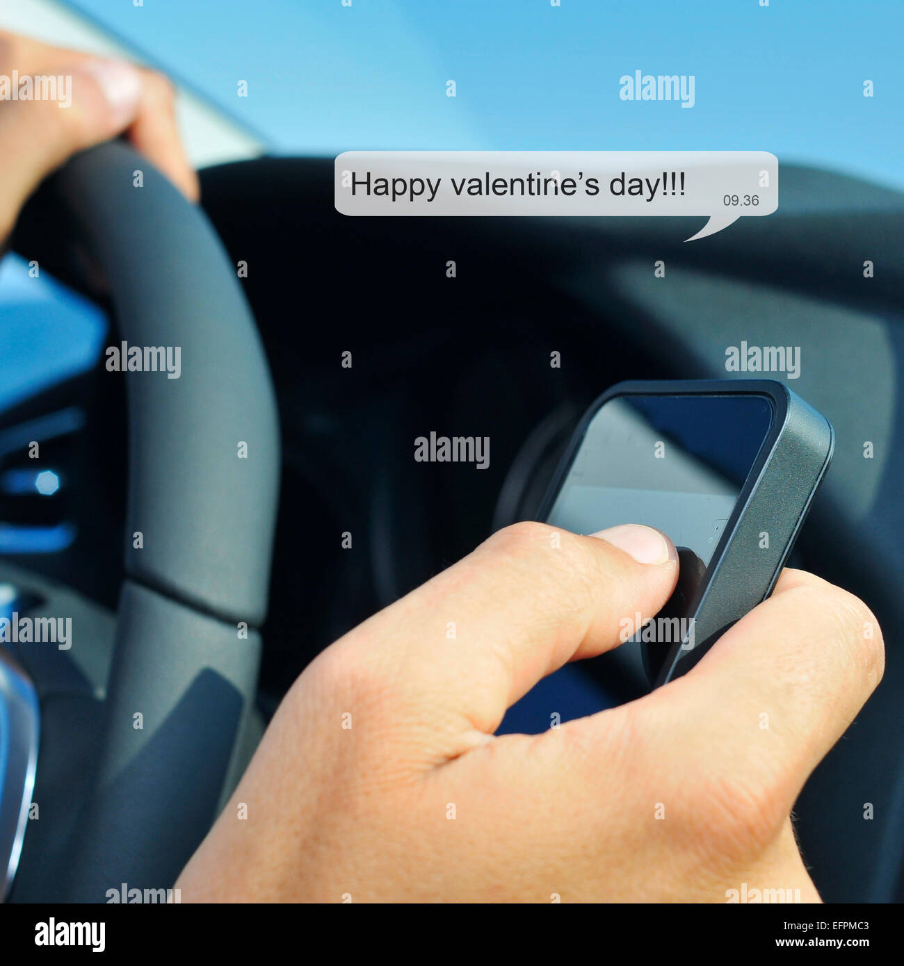 a man driving a car reads or sends the text message: happy valentines day Stock Photo