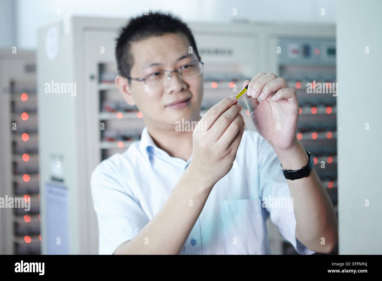 Worker looking at product in ecigarette factory - Stock Image