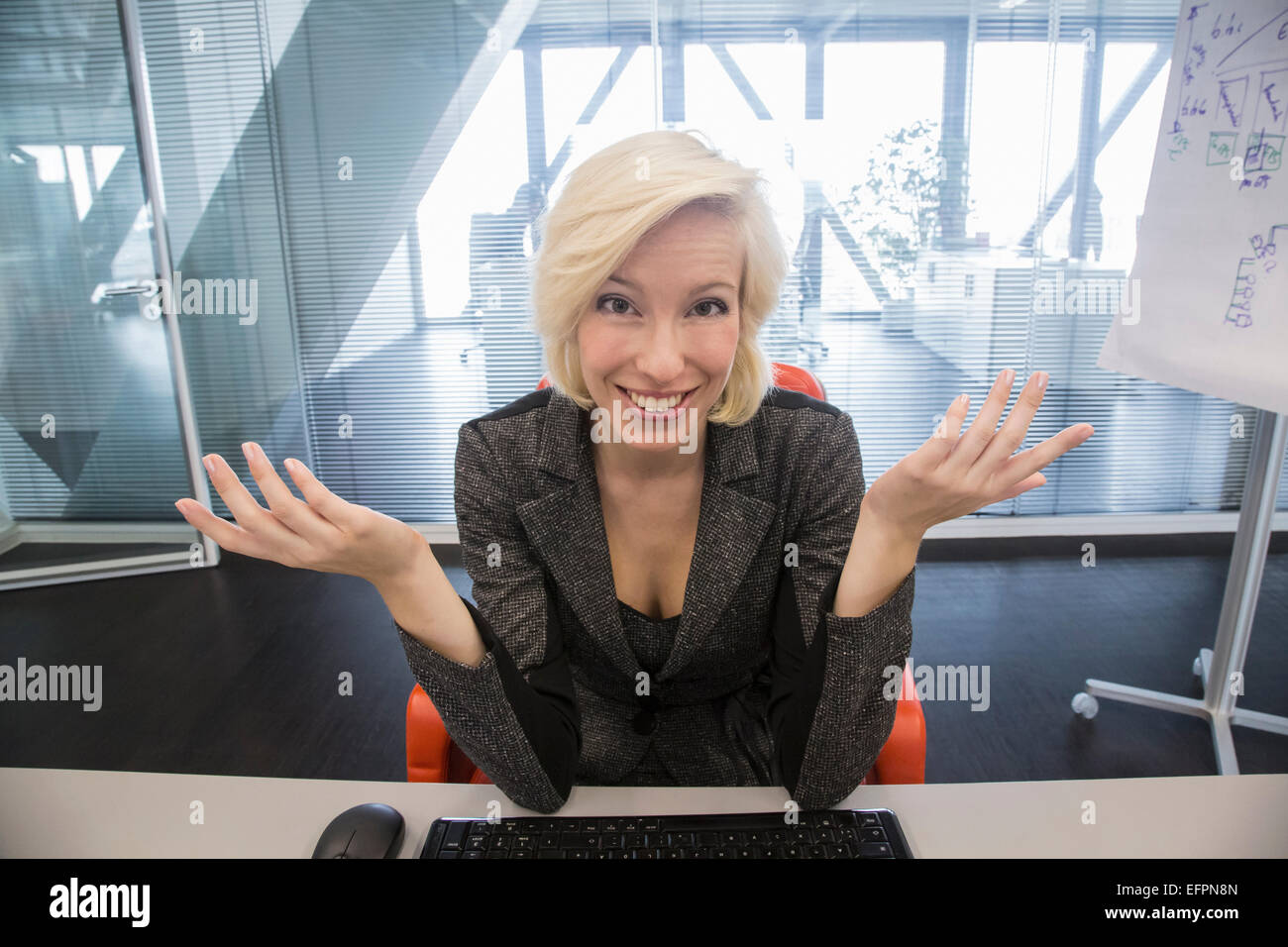 Mid adult woman shrugging, portrait - Stock Image