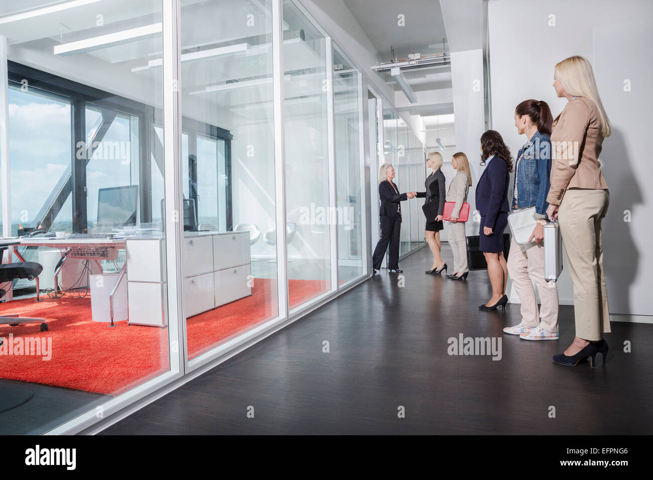Women queueing outside interview room Stock Photo