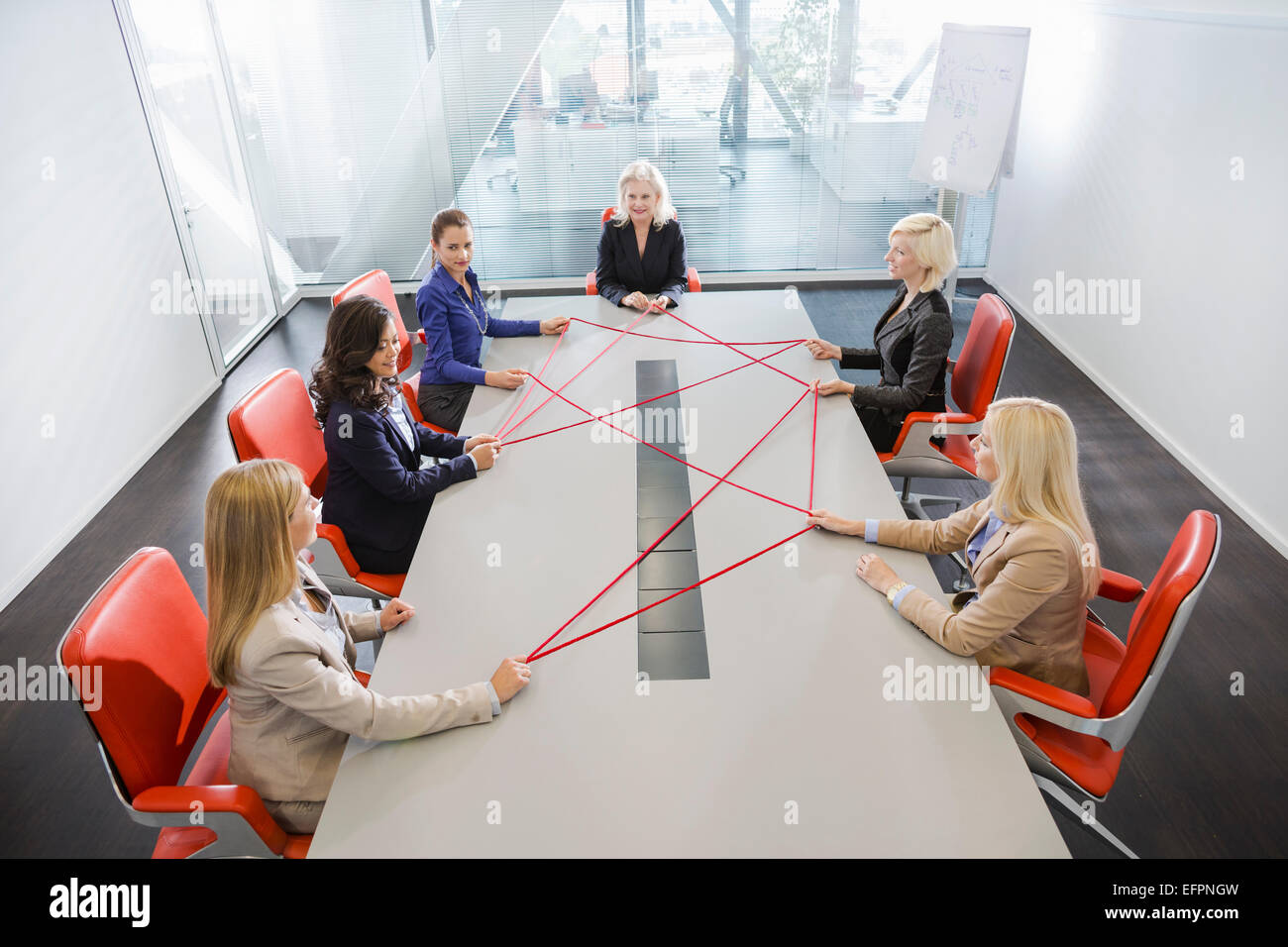 Women problem solving at conference table - Stock Image