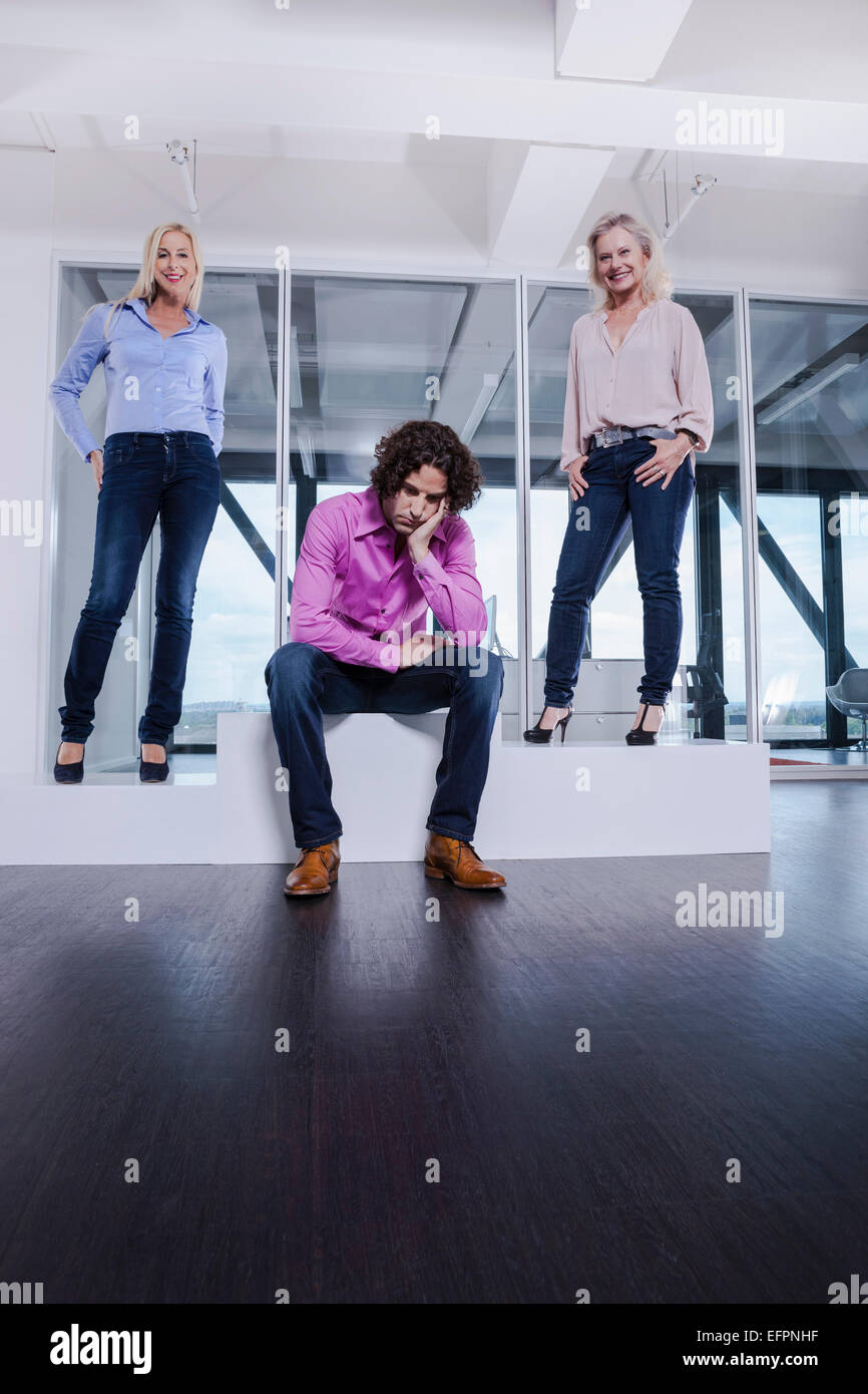 Man sitting on podium with head in hands with female colleagues - Stock Image