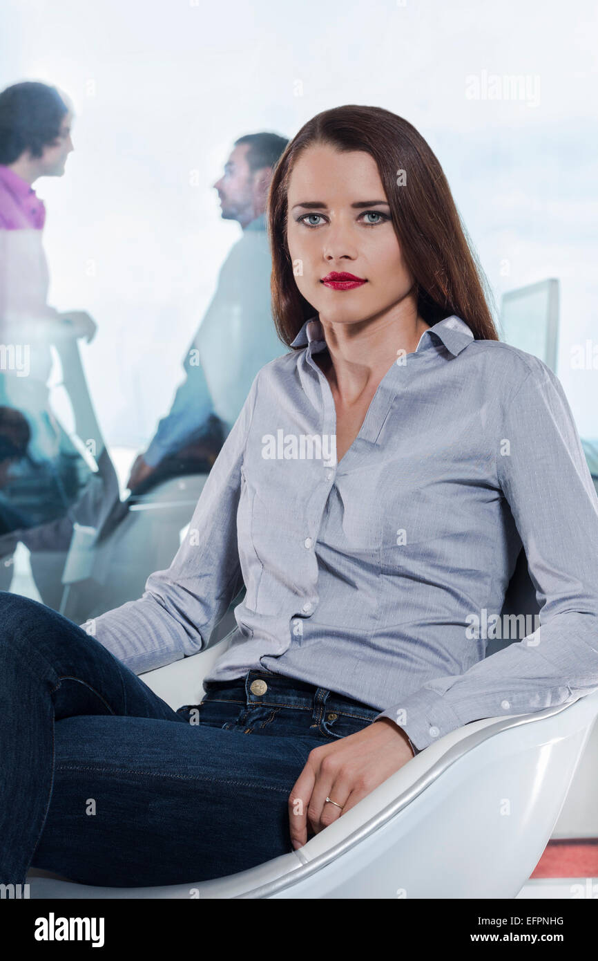 Mid adult woman wearing grey shirt, portrait - Stock Image