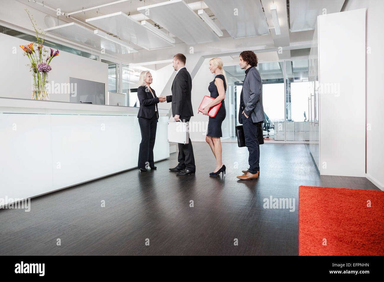 Woman shaking hands with visitors at reception - Stock Image