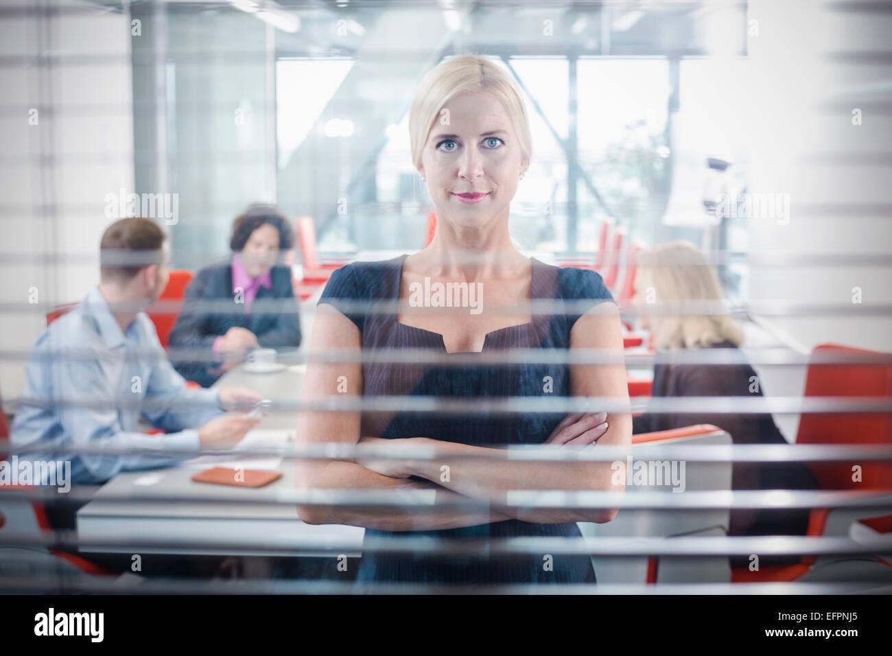 Mid adult woman behind window - Stock Image