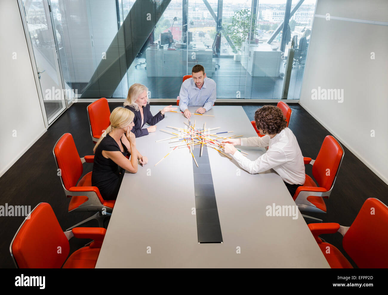 Colleagues problem solving in conference room - Stock Image