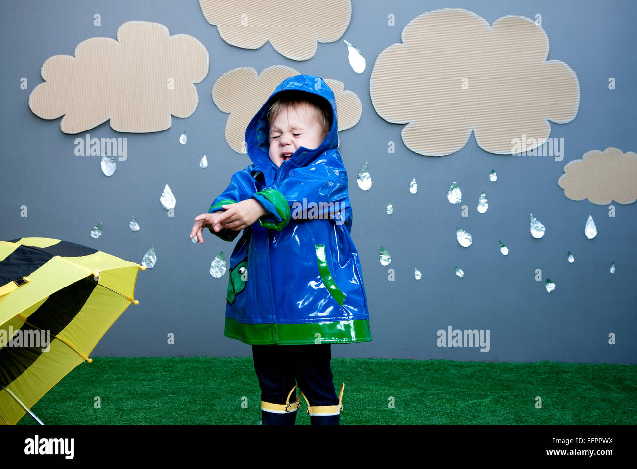 Baby girl with rain cutouts - Stock Image