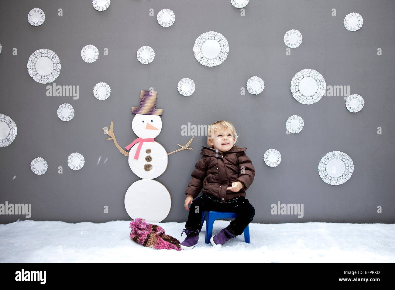 Baby girl with snowflake and snowman cutouts - Stock Image