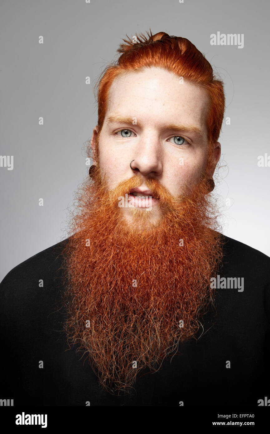 Studio portrait of staring young man with red hair and overgrown beard - Stock Image