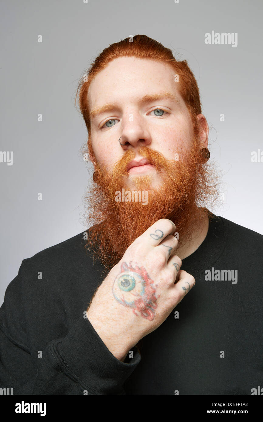 Studio portrait of young man with red hair stroking beard - Stock Image