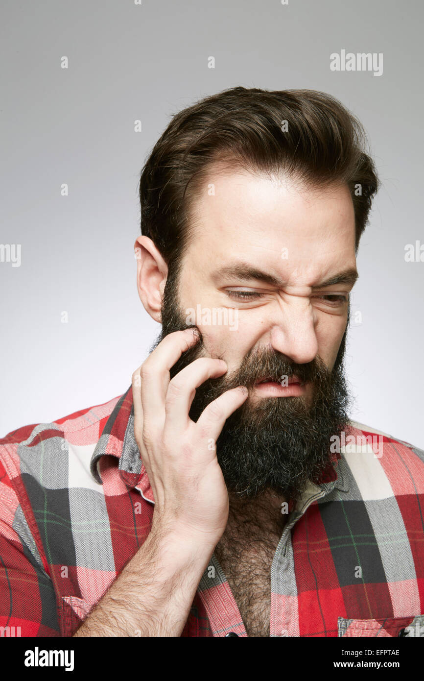 Studio portrait of young man scratching overgrown beard - Stock Image