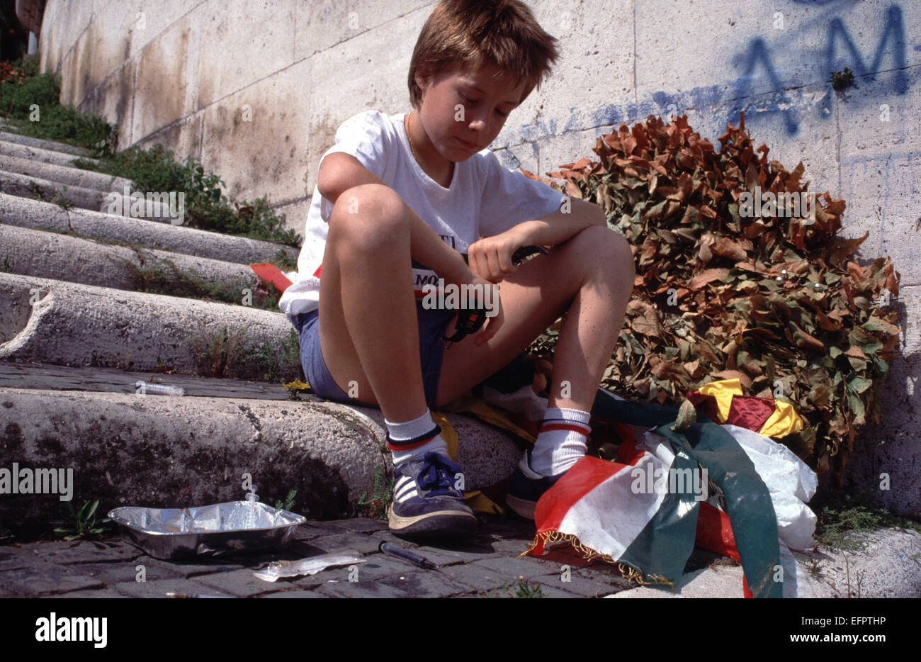 Young boy on the steps by the Tiber river in Rome surrounded by used needles illustrating a drug problem - Stock Image