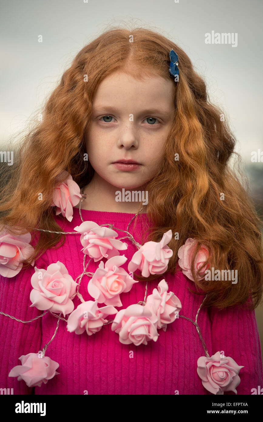 Portrait of a little girl with a rose garland around her neck. - Stock Image