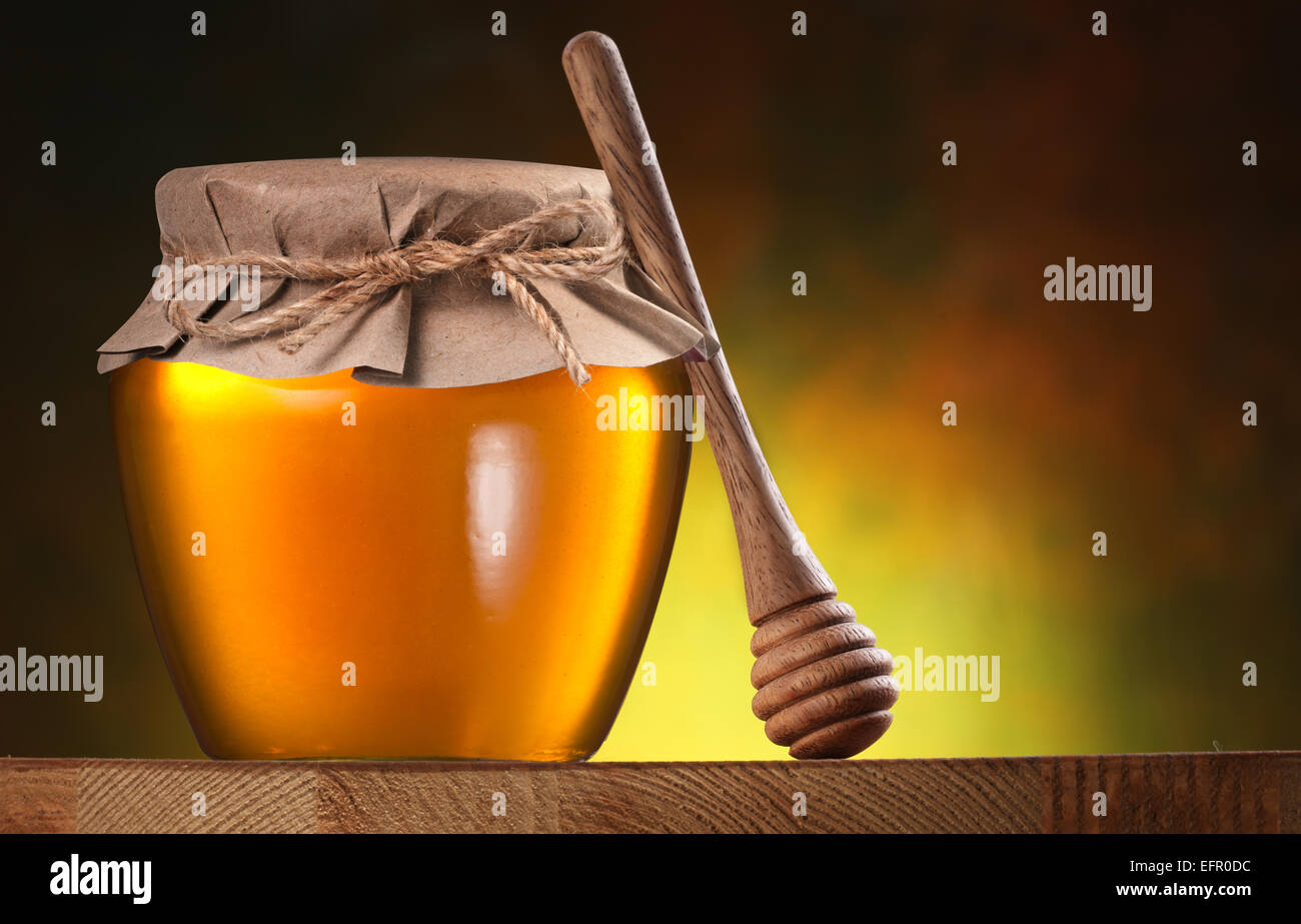 Glass can full of honey and wooden dripper on brown background. - Stock Image