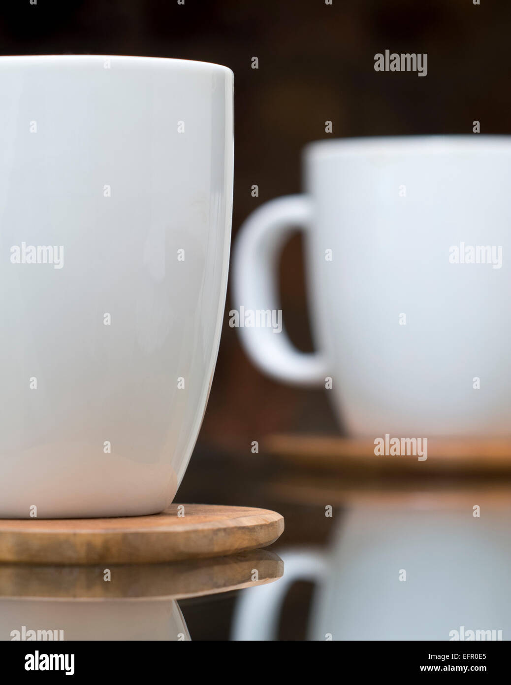 48f61bacda6 Reflected white ceramic mugs on wooden coasters on glass table Stock ...