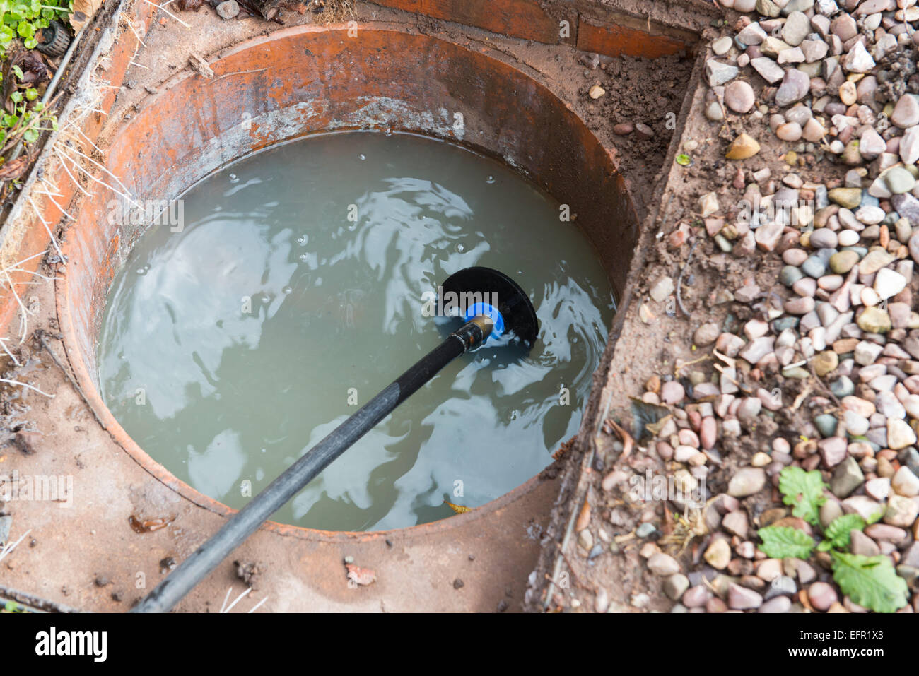 Clearing a blocked house drain with drain rods Stock Photo
