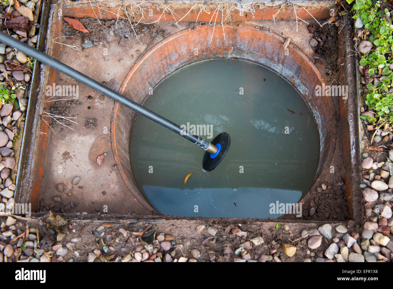Clearing a blocked house drain with drain rods - Stock Image