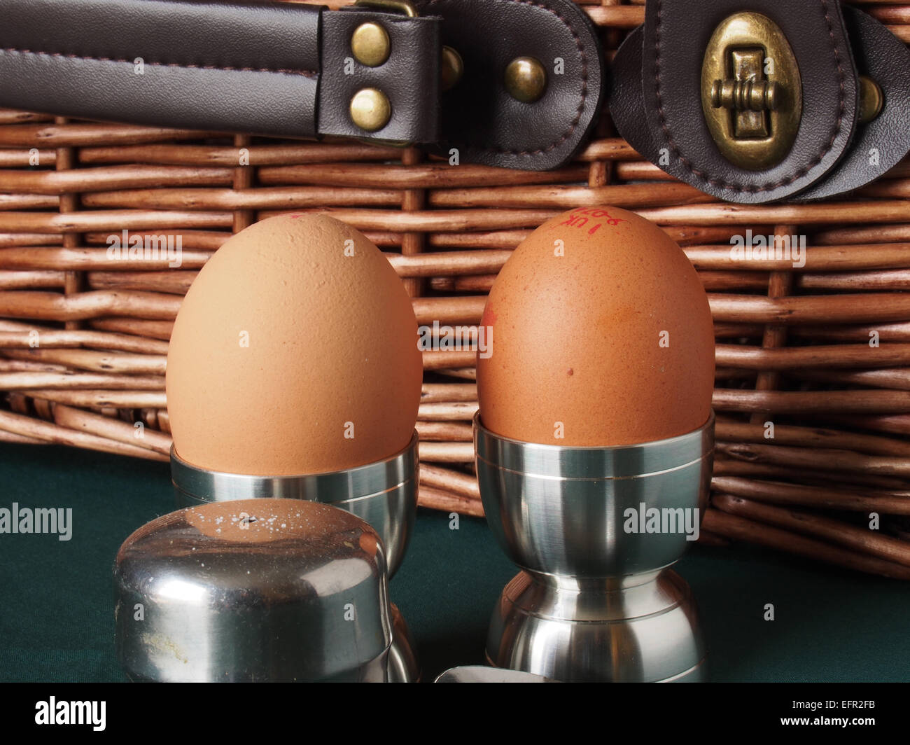 Boiled eggs in egg cups with salt cellar and picnic hamper - Stock Image