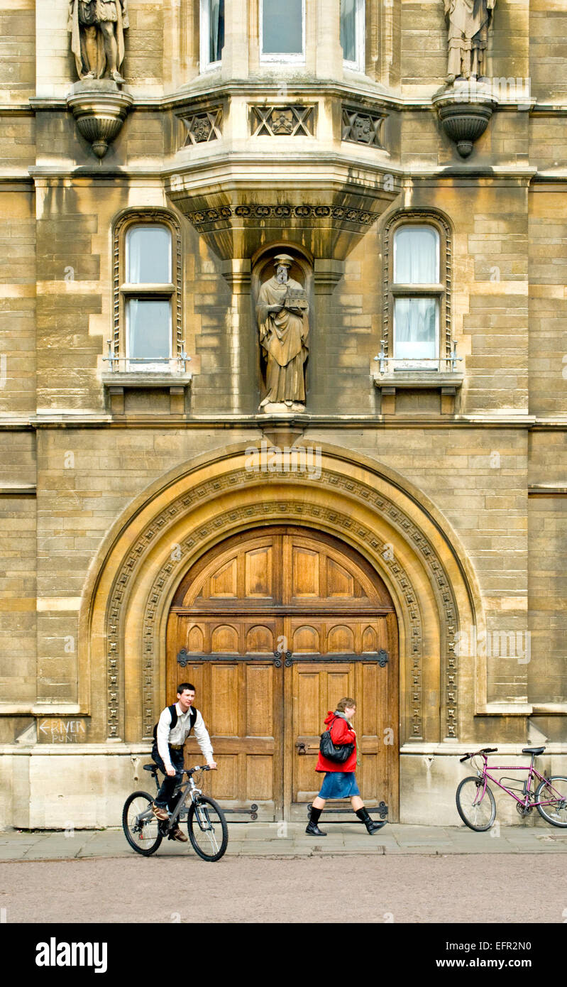 Cambridge, England, UK. Man cycling and woman walking past Gonville and Caius College in Kings Parade - Stock Image